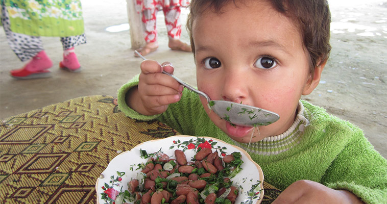 Feed the Future, through USAID, has trained thousands of Tajik women to make healthy meals, such as the kidney bean salad this child is eating.