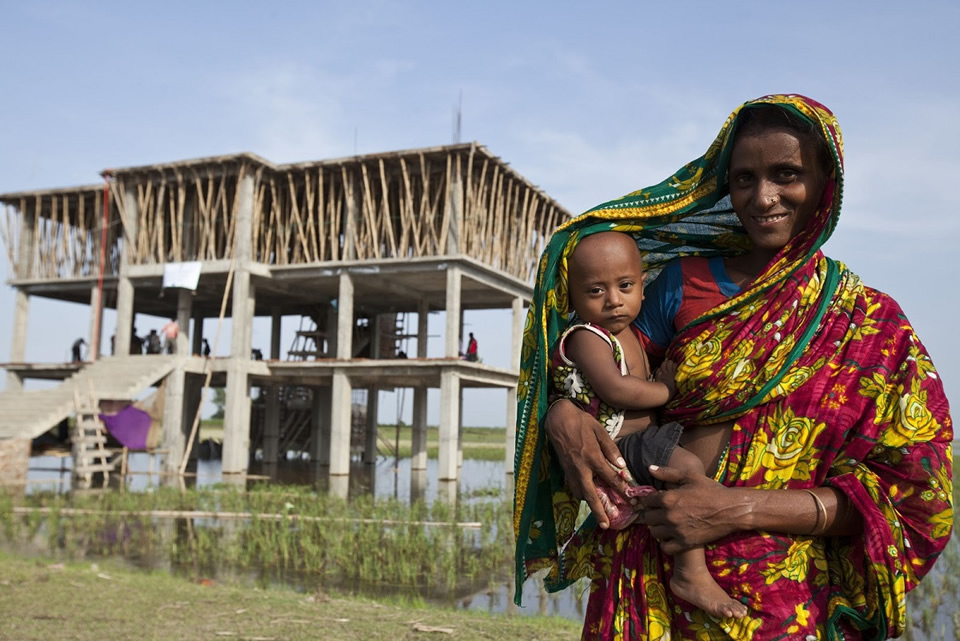 A woman holds her infant in front of a house. Photo credit: Abir Abdullah