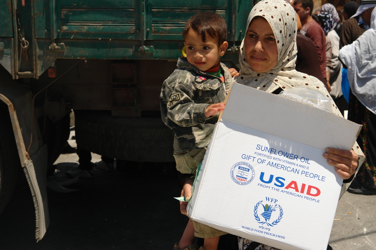 Image of woman and child collecting box of USAID-WFP donated food in Hebron.