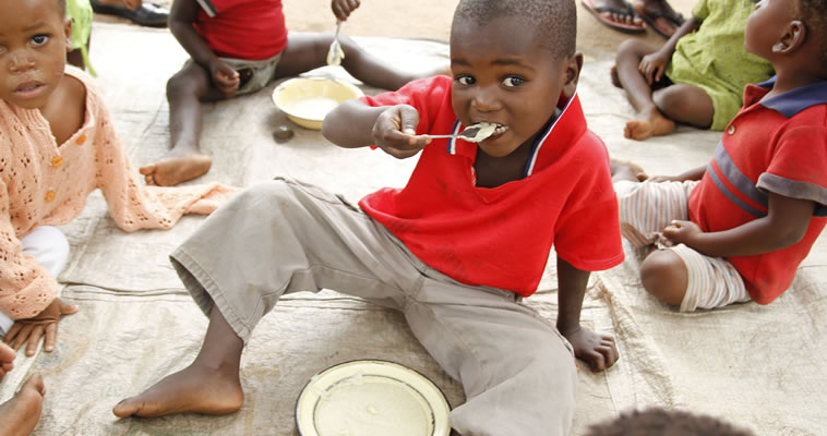 A young Malawi boy eats a snack. Photo credit: Megan Collins, Catholic Relief Services.