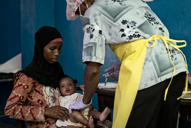 A mother holds her baby while a health worker administers a shot.