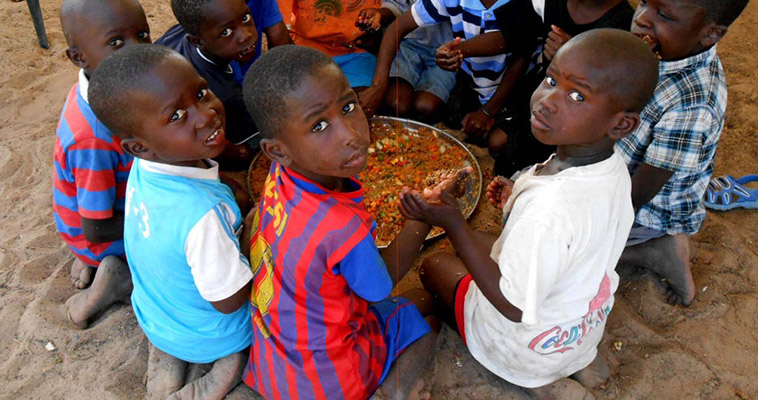 Children eat a hearty lunch provided for them at a farmer training in Senegal.
