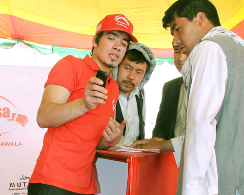 Several young Afghan men listen as a representative from M-Paisa describes how mobile bill pay works.