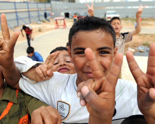 Internally displaced Libyan children flash victory signs while playing in a refugee camp in the eastern rebel stronghold of Beng