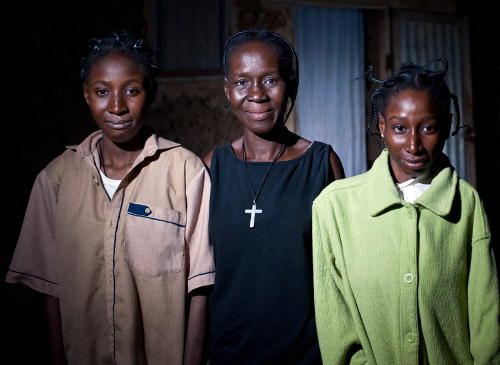 Florence, Rosalie, and Diane Ouedraogo stand outside their home on a cool evening.
