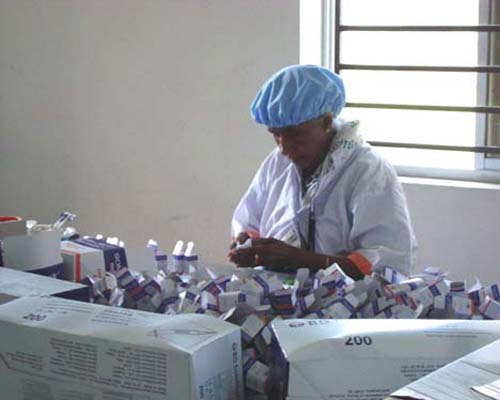 A Social Marketing Company employee packs injectables at a warehouse.