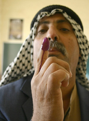 An Iraqi man looks at his finger stained with indelible ink at a polling station in Basra, Jan. 30, 2005.
