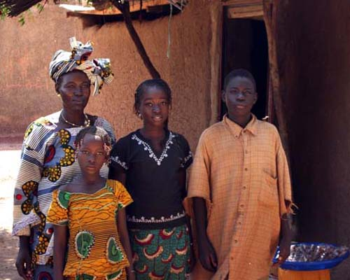 Aïssata Konaté with her children in front of their new house.