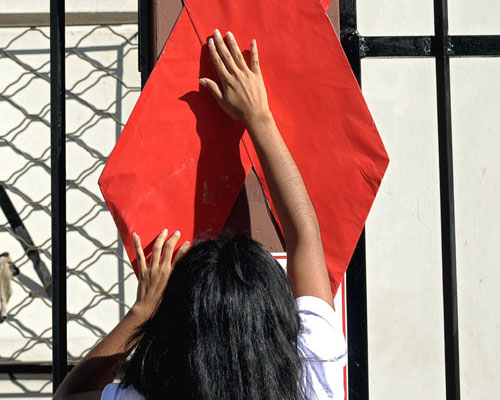 An activist sets up a red ribbon during the commemoration of the World AIDS Day in San Salvador, on December 1, 2010.