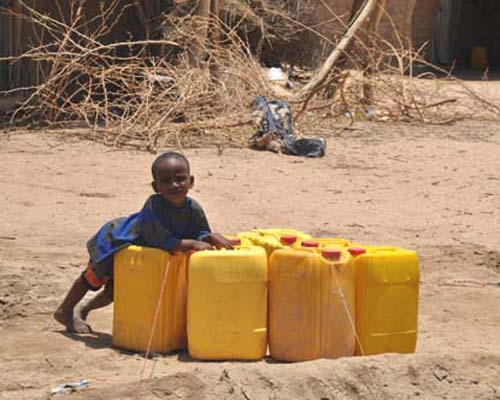 An Ethiopian child at play after water is delivered to the Dire Dawa pastoralist camp.