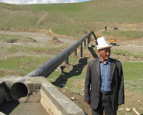 Abibilla Kimsanov, head of the water users association, at the newly restored aqueduct in the Zulpuev municipality.