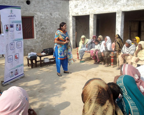 Women from Pakistan's Khanewal district participate in a meeting conducted by a FALAH-trained health worker on healthy timing an