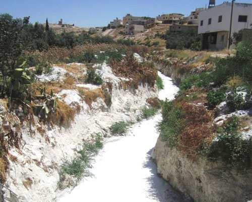 A slurry-filled Hebron waterway, prior to USAID's intervention.