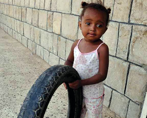 A 3-year-old girl in Lahj plays with a tire.