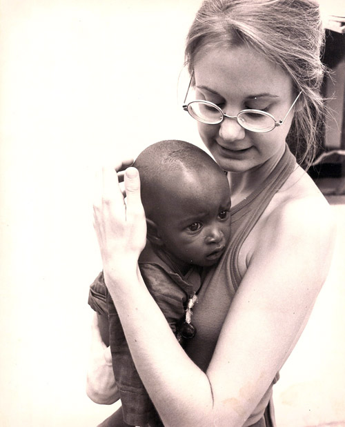 In the mid-1970's, Joan Wadelton, a Peace Corps volunteer from Princeton, N.J., holds a child at a maternal and child center.