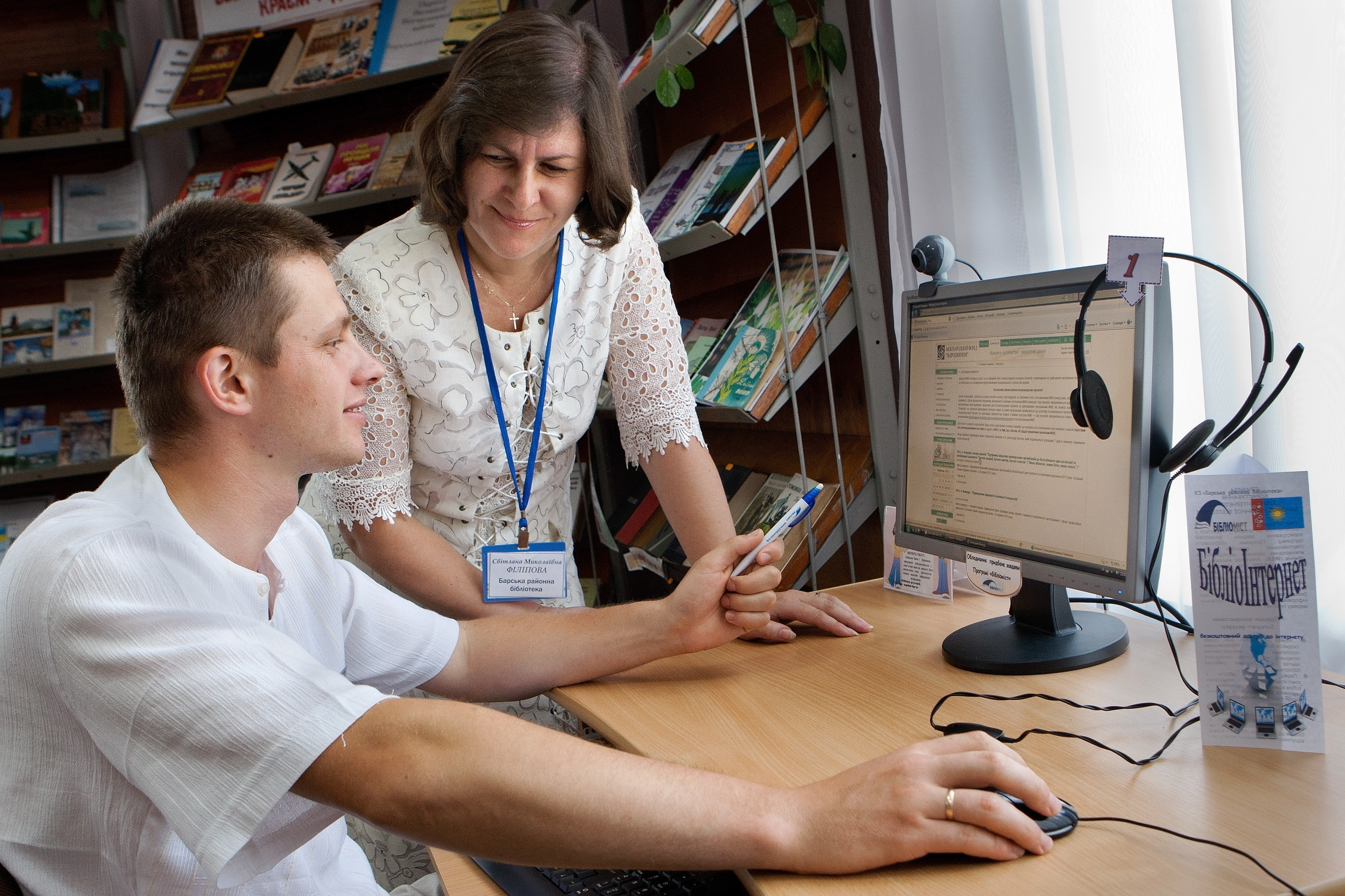 A Library Consultant teaches a patron about using the Internet.