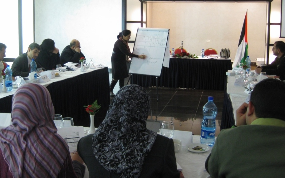 Image of woman presenting to an audience of men and women at a training at the Ministry of Public Works and Housing.
