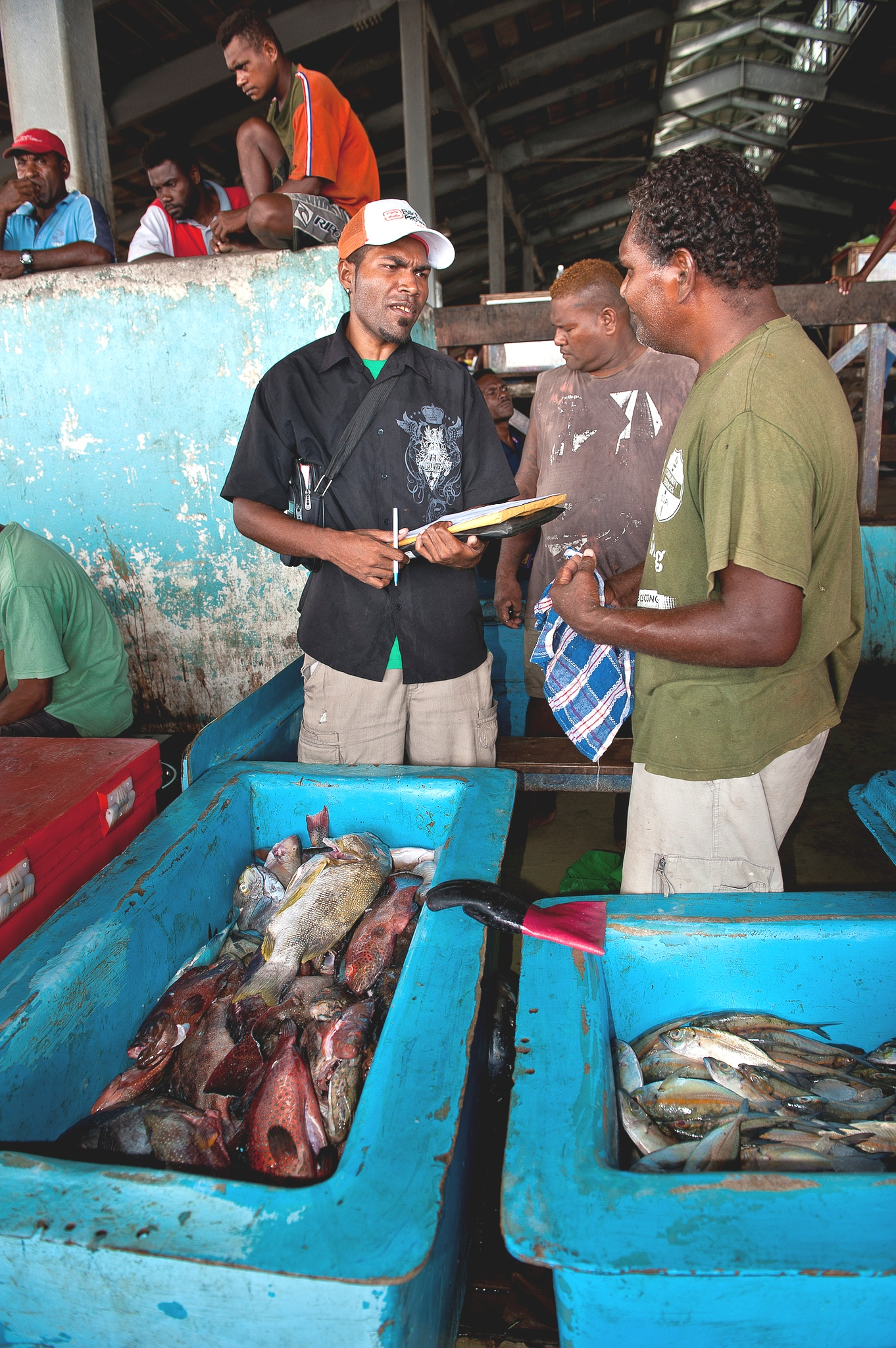 Patrick Ketete, surveyor for the Ministry of Fisheries, interviews a vendor at the Honiara main market.