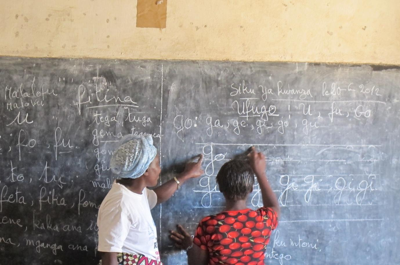 Two individuals write on a chalkboard