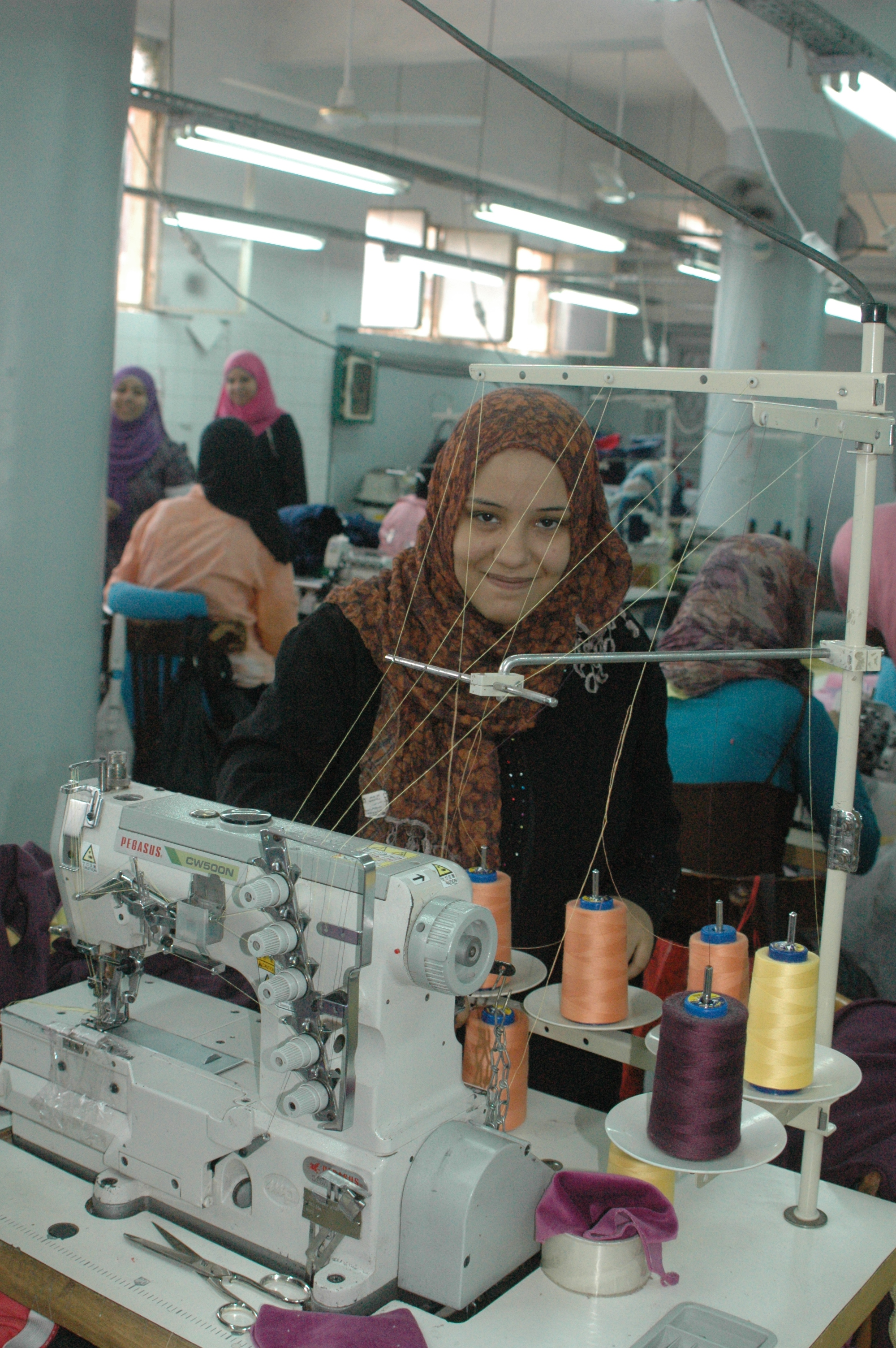 Woman works at sewing machine in small clothing factory