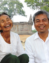Im Chaem, left, sits beside Youk Chhang, director of the Documentation Center of Cambodia, at Preah Vihear Temple on top of the