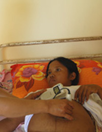 A health center midwife performs a check-up on an expectant mother.