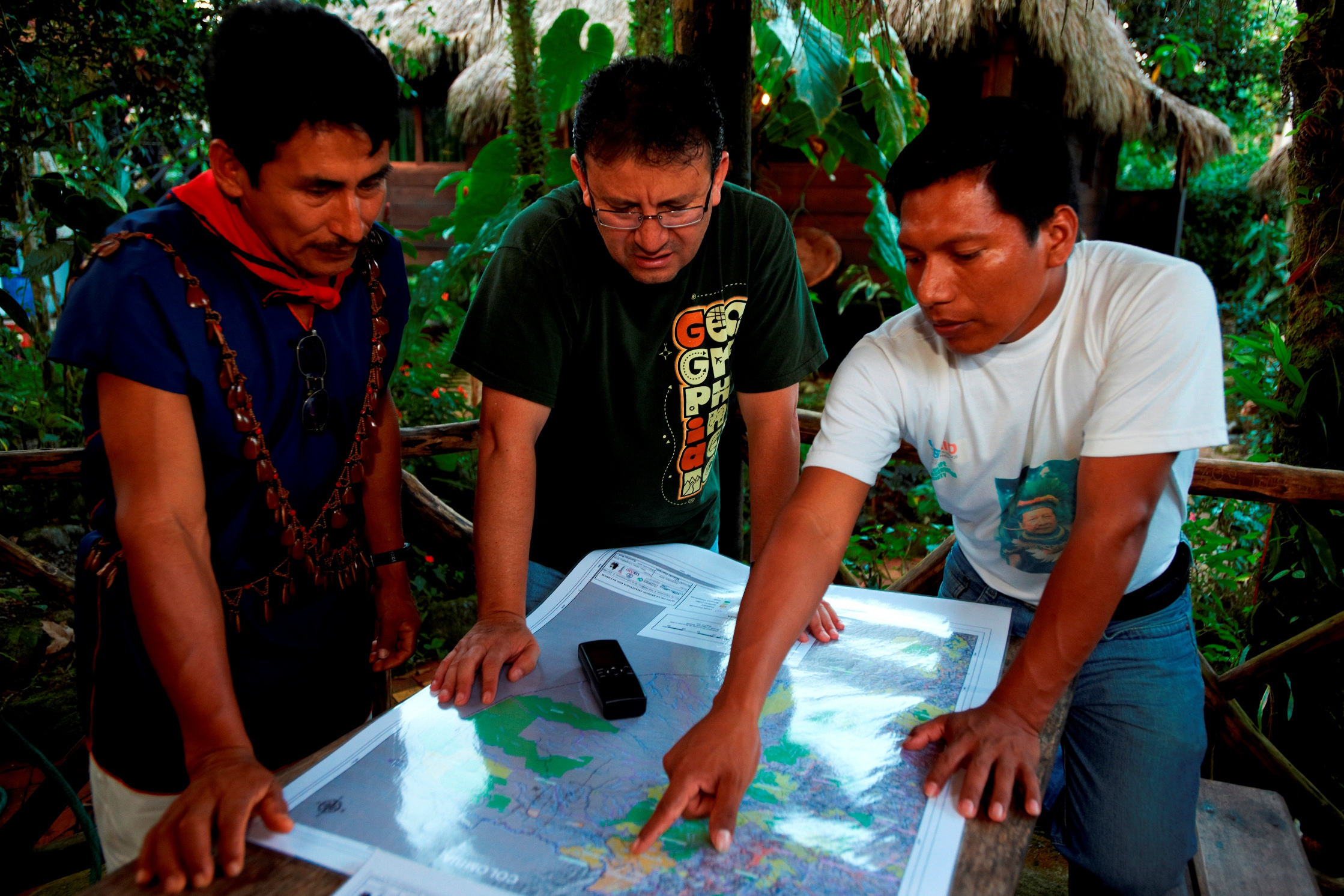 William Lucitante, right, confers with Marcelo Guevara of The Nature Conservancy, center, and a Cofan ranger.