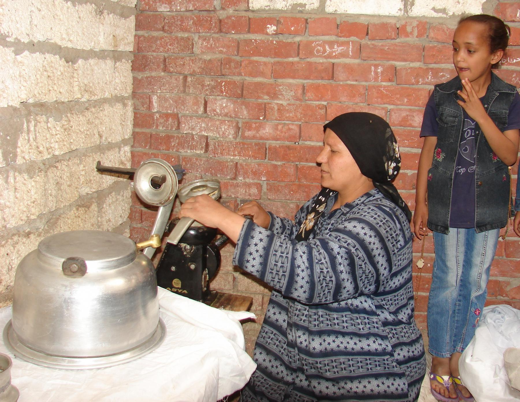Image of Egyptian woman working while her young daughter looks on.