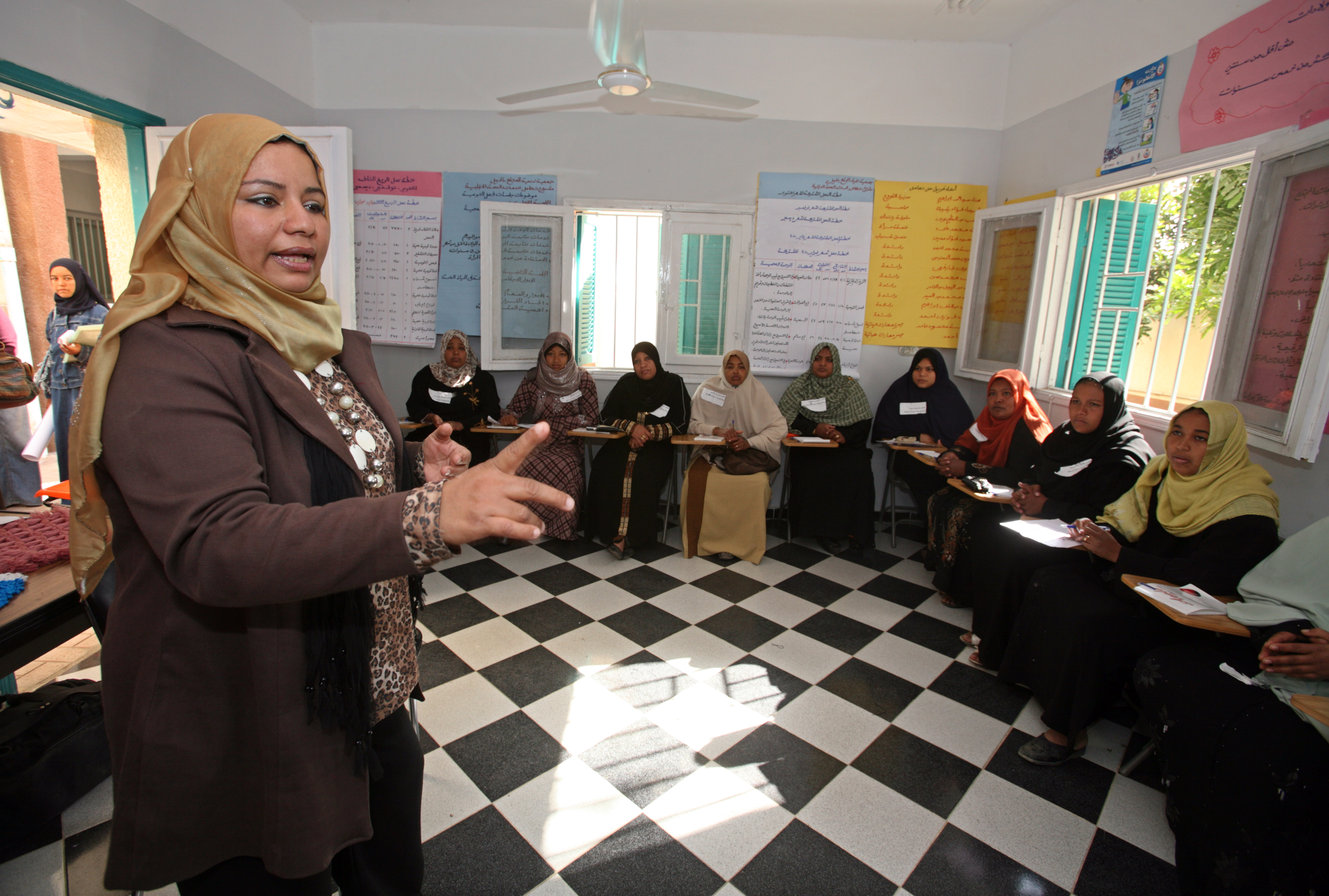 Image of female Community Development Worker in Egypt speaking to an audience of women.