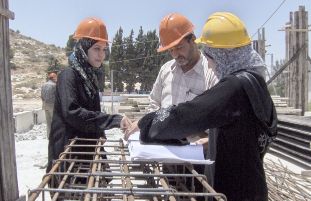 Two woman and a man review construction plans in the West Bank