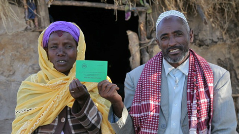 An Ethiopian couple proudly display their jointly issued land certificate, issued under a USAID project in conjunction with the