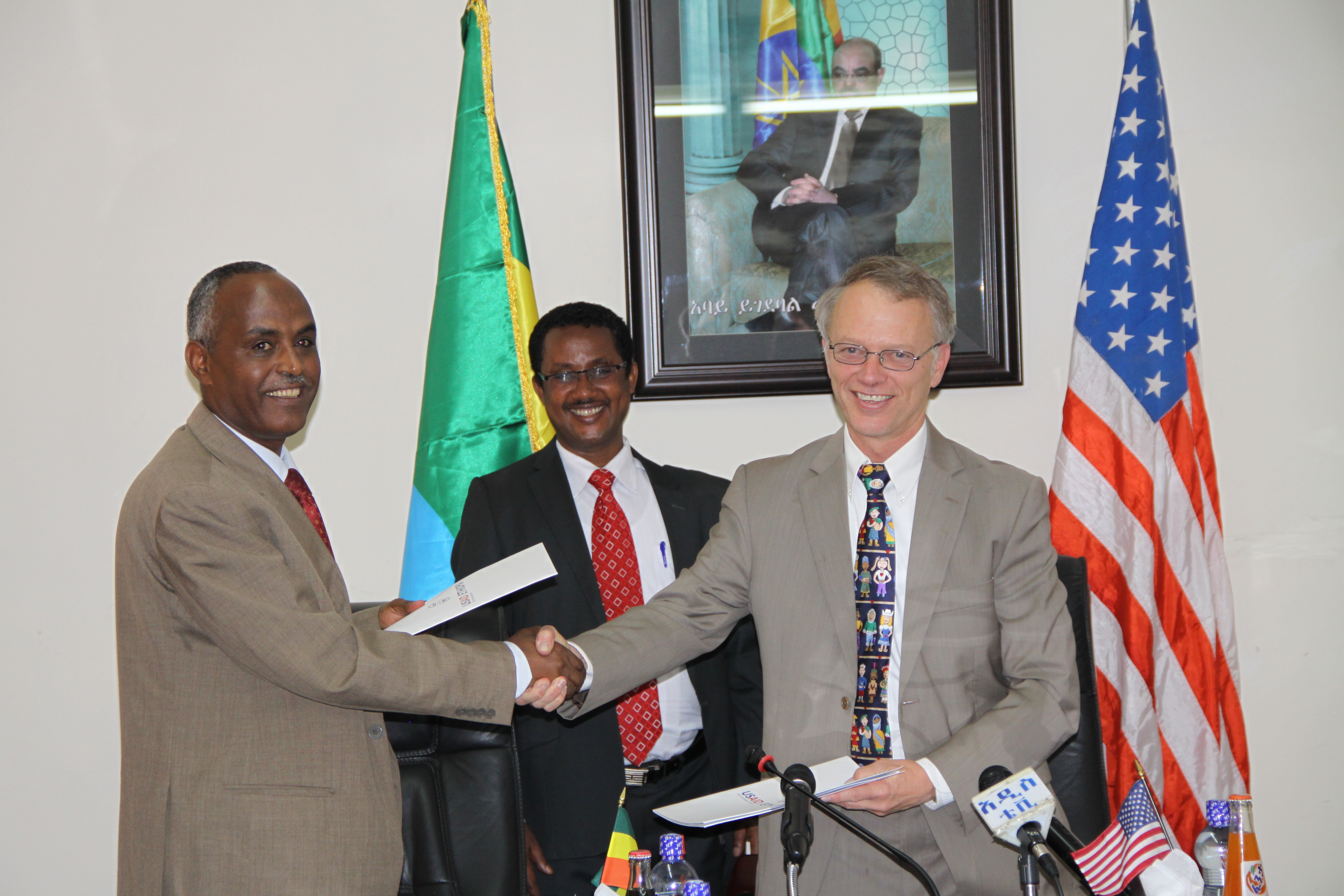 Addis Ababa Deputy Mayor Abate Sitotaw (left) and USAID Mission Director Dennis Weller shake hands after signing a new agreement