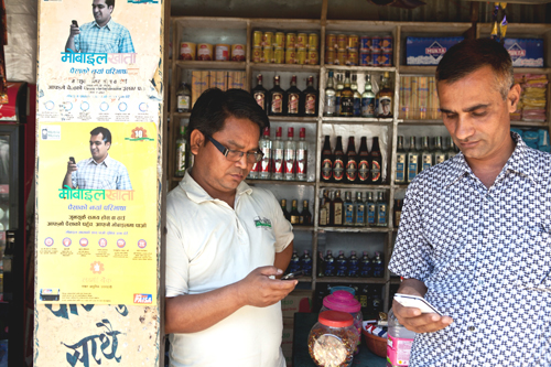 Krishna Prasad Bhattarai, right, uses his cell phone to transfer money to his daughter's account for payment of her school fees.