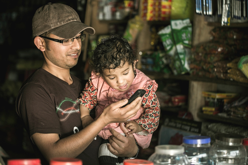 A young child looks on as his father, a small shop owner, uses his low-cost cell phone to pay his suppliers.