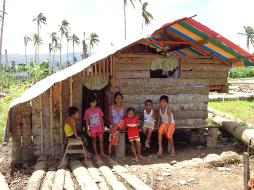 Jeneth Cervantes and her five children in their newly built, USAID-funded emergency shelter.