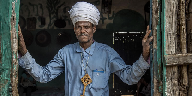 Banner image of an Ethiopian religious leader standing in a doorway. Photo credit: Karen Kasmauski/MCSP.
