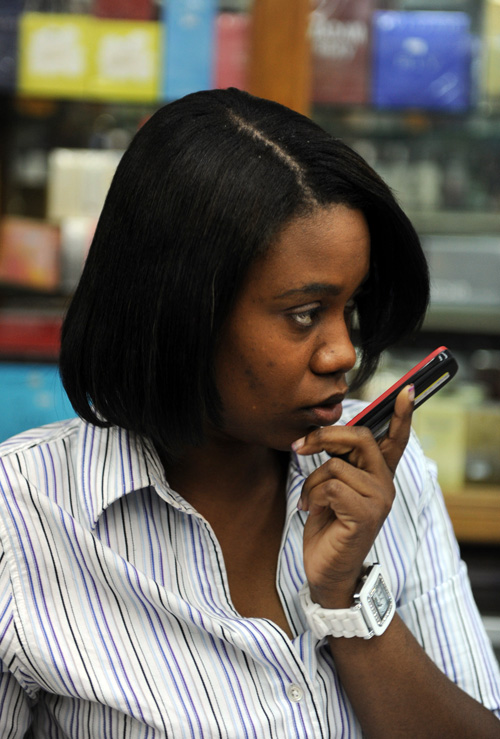 A supermarket employee in Port-au-Prince, Haiti, uses her mobile phone, March 3, 2011.