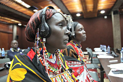 Kenyan women wearing their colorful traditional beads and fabrics wear headphones as they listen to a presentation.