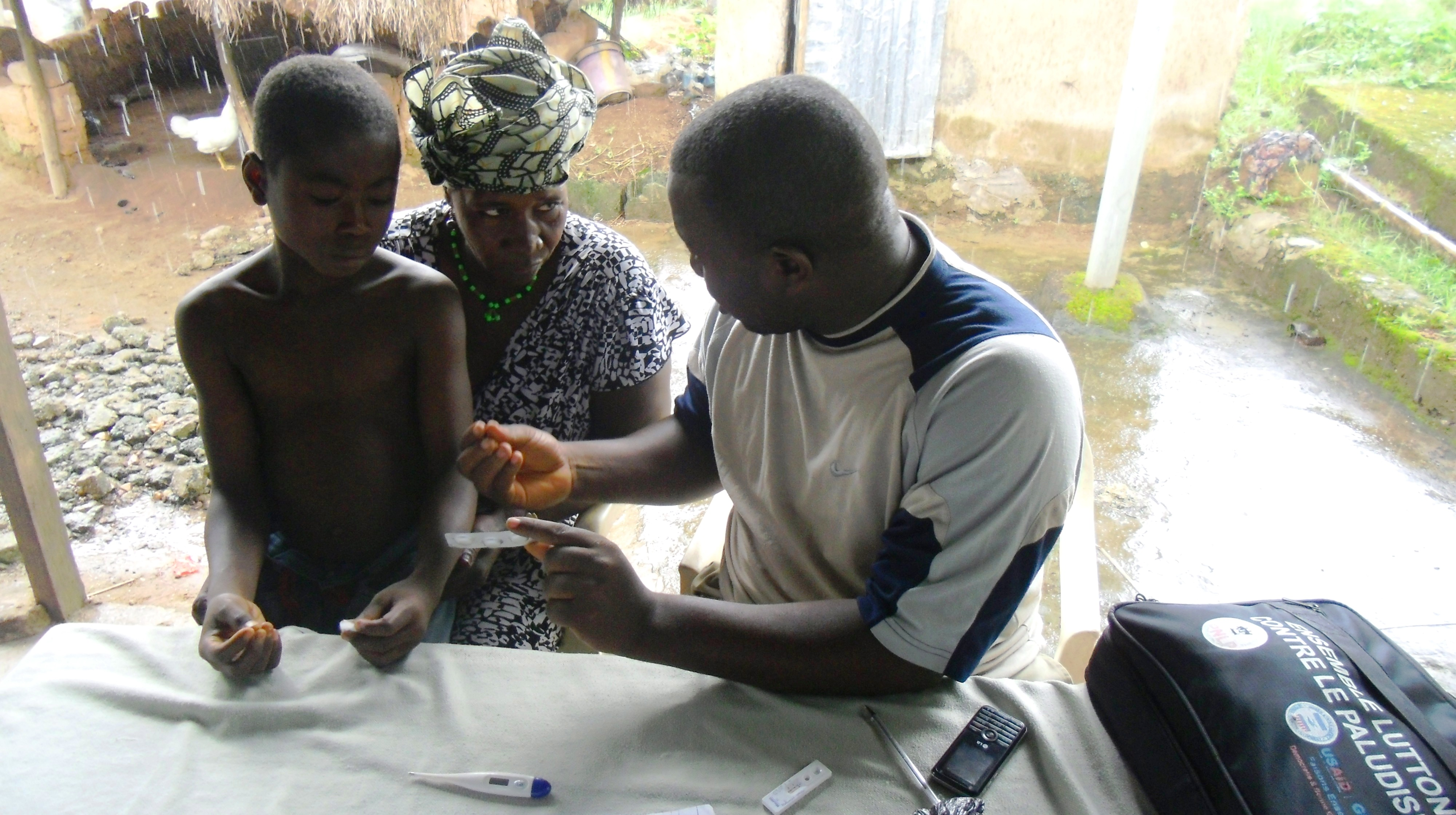 A health worker tests a boy for malaria while his mother listens.