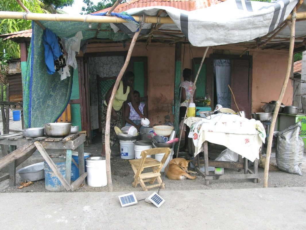 Women charge their Enèji Pwòp solar products in front of their market stall.
