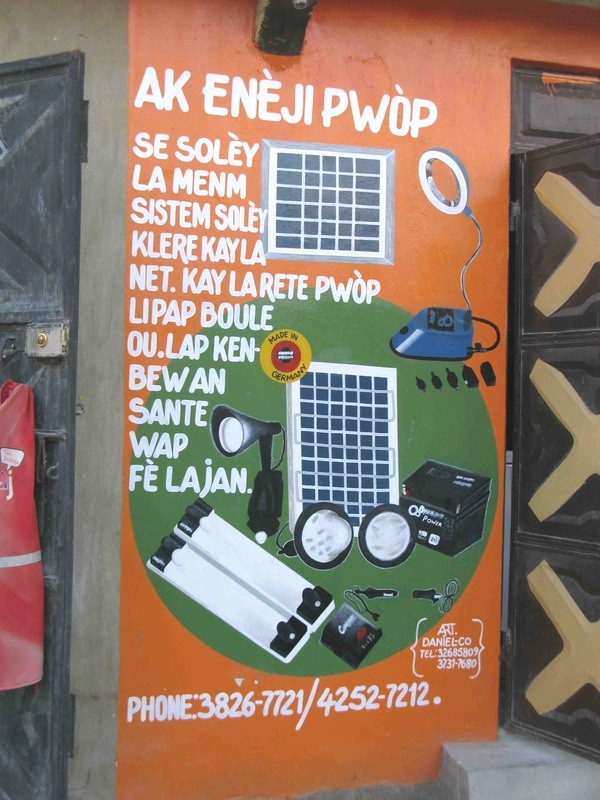 An Enèji Pwòp reseller painted an illustrative ad on her store to promote the solar products she sells.