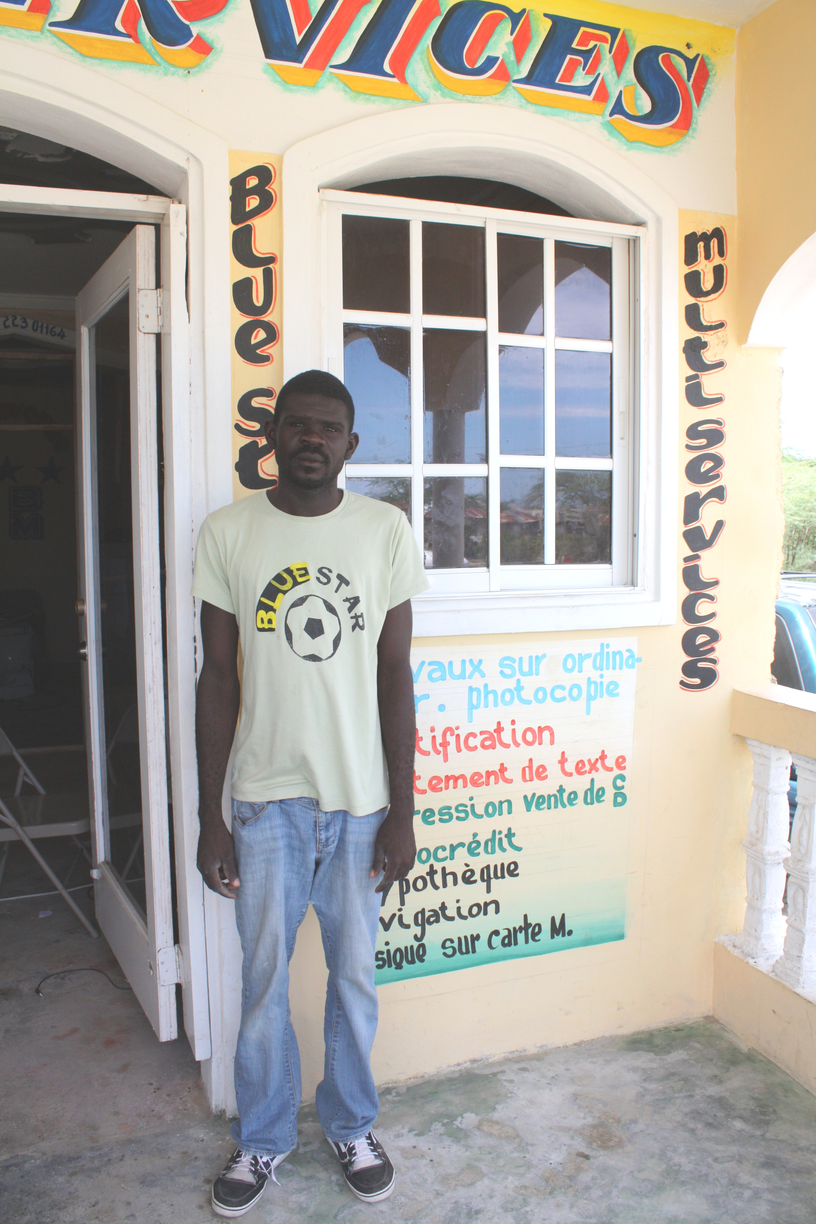 Cadet Luxon, the manager of Cyber Café, stands in front of his shop in Caracol, Haiti, in August 2013.