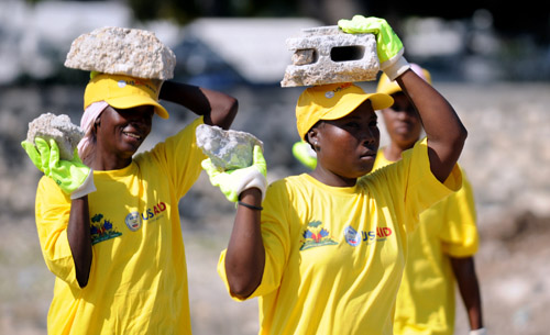Two women carry rubble to be crushed and recycled for use in earthquake recovery efforts in Carrefour, Haiti, Feb. 15, 2011.