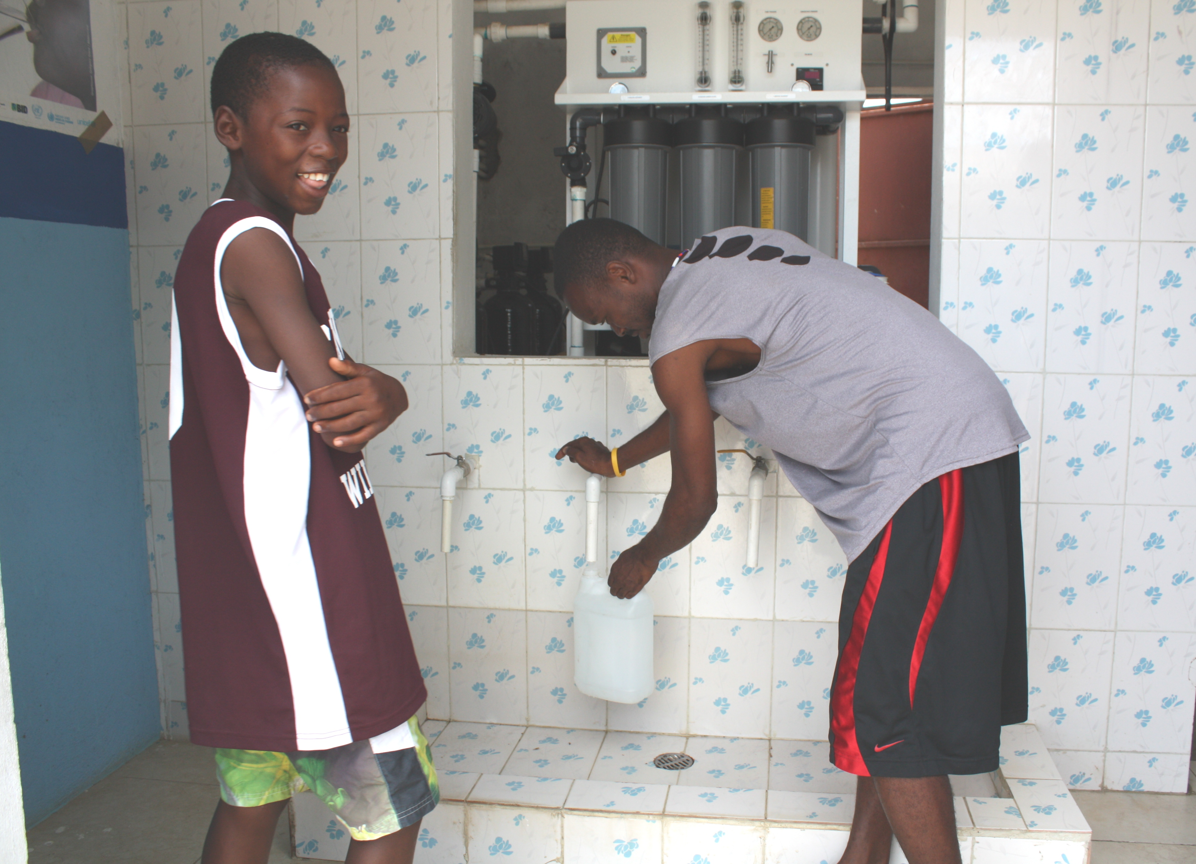 A boy buys clean drinking water from Pierre Ricardo at a reverse osmosis water treatment business in Caracol, Haiti.