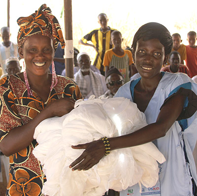 Two Senegalese women receive insecticide-treated bednets through a USAID program.
