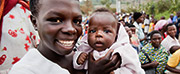 Photo of woman holding a baby and smiling