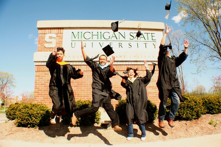 """Image of four Indonesian students celebrating in front of the """"Michigan State University"""" entrance sign"""