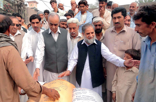 Pakistan Minister of Agriculture Arbab Ayub Jan, center, distributes wheat seed to flood-affected farmers in Khyber Pakhtunkhwa.
