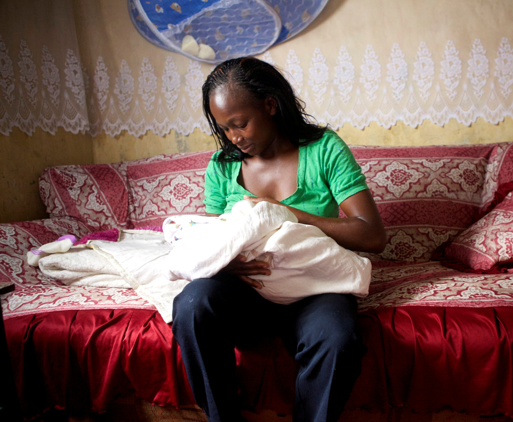 Lillian Kambura holds her newborn son, Paul, in her home in Mwiki, Kenya, as she waits for her three-day postpartum home visit.