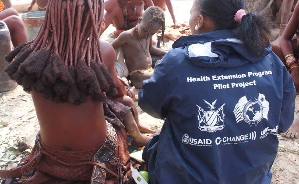 A woman wearing a C-CHANGE jacket sits with a group of women and children.